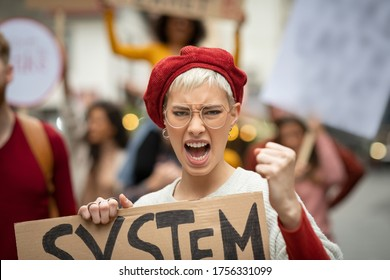 Portrait of angry woman shouting in rally fighting for her rights. Furious woman at climate change and save planet strike looking at camera. Feminist raising voice and hold protest sign for rights.