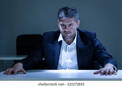 Portrait of angry, young businessman sitting at the table