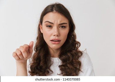 Portrait of an angry young casual brunette woman pointing at camera isolated over white background