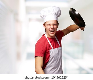 portrait of angry young cook man hitting with pan indoor
