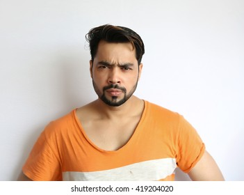 Portrait of a angry young indian man against white background