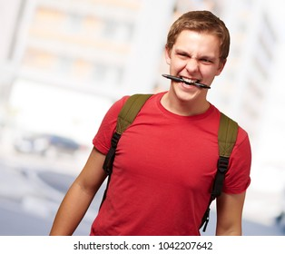 portrait of angry young man biting pen against a modern building