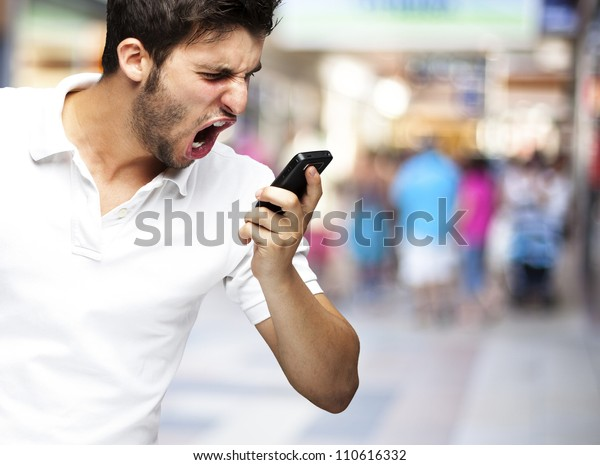 portrait of angry young man shouting using mobile at a crowded m