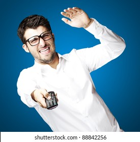 portrait of angry young man using tv control over blue background