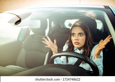 Portrait, angry young sitting woman pissed off by drivers in front of her and gesturing with hands. Road rage traffic jam concept. Woman is driving her car very aggressive and gives gesture with his f