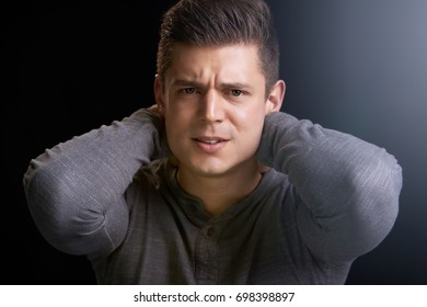 Portrait of angry young white man with hands behind his neck
