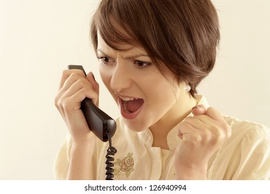 Portrait of angry young woman with a phone on a light background