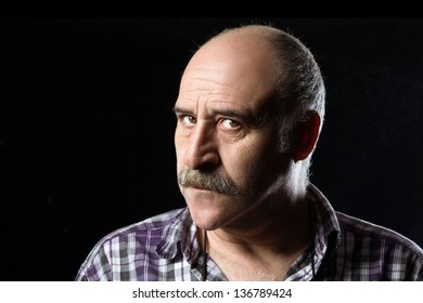 Portrait of annoyed bald man with a big mustache expressing anger