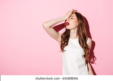Portrait of annoyed beautiful woman placing back hand on forehead as if to say oh the tragedy of it all isolated over pink background