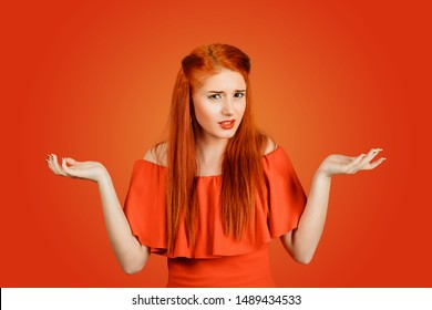 Portrait annoyed looking woman arms out shrugs shoulders who cares so what I don't know isolated on a red background. Negative human emotion, facial expression body language life perception attitude