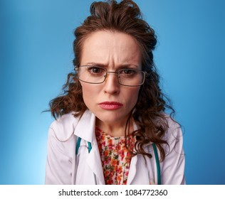 Portrait of annoyed pediatrician doctor in white medical robe looking in camera on blue background