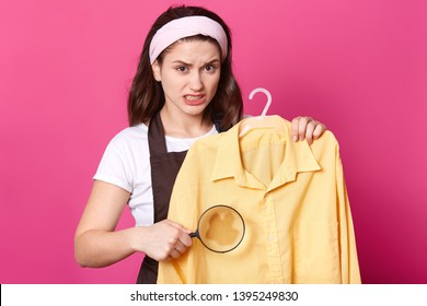 Portrait of annoyed upset woman stnading with yellow shirt on hanger, holding loupe, making stain bigger, irritated with dirt on clothes, having disappointed facial expression. House chores concept.