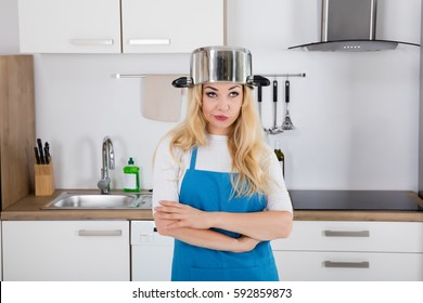 Portrait Of An Annoyed Young Woman With Cooking Pan On The Head Standing In Kitchen