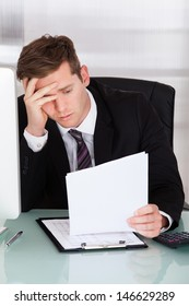 Portrait of Anxiety businessman sitting in office holding paper