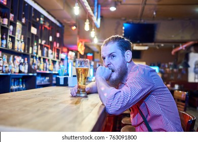 Portrait of anxious bearded man looking worried and angry while watching sports match on TV sitting at bar counter in pub with tall glass of beer, copy space