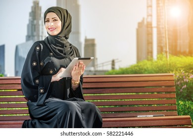 Portrait of an Arab businesswoman holding a tablet. Arab businesswomen in hijab holding a tablet in the street against the backdrop of the skyscrapers of Dubai. The woman is dressed in a black abaya