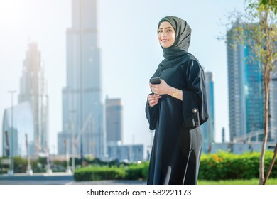 Portrait of an Arab businesswomen. Arab businesswomen in hijab talking on cell phone on the street on a background of skyscrapers of Dubai. The woman is dressed in a black abaya