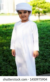Portrait of Arab little boy while standing and looking at the camera wearing Gulf kandura dress