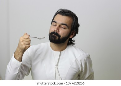 Portrait Of An Arab Man Eating With Spoon  And Enjoying The Taste With His Eyes Closed