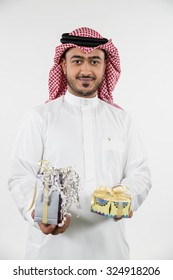 Portrait of Arab man holding gift boxes