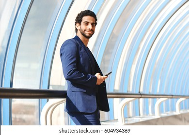 Portrait of Arab man in a suit holding a phone leaning on railing in glass transition