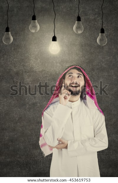 Portrait of Arabian young businessman thinking idea while looking at the lightbulb