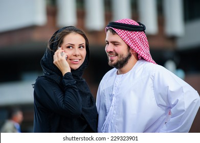 Portrait of Arabic dressed yang couple play with mobile phone..