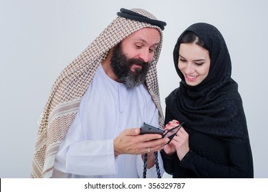 Portrait of Arabic way dressed couple play with mobile phone
