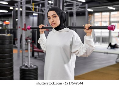 portrait of arabic young female exercising with weights in gym, she stands looking at camera, serious and confident, wearing white sportive hijab