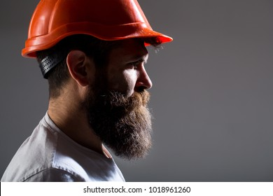 Portrait architect builder, civil engineer working. Builder in hard hat, foreman or repairman in the helmet. Bearded man worker with beard in building helmet or hard hat. Man builders, industry.