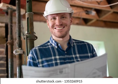 Portrait Of Architect Inside House Being Renovated Studying Plans