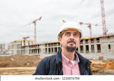 Portrait of architect at work with helmet in a construction site,reads the plan.