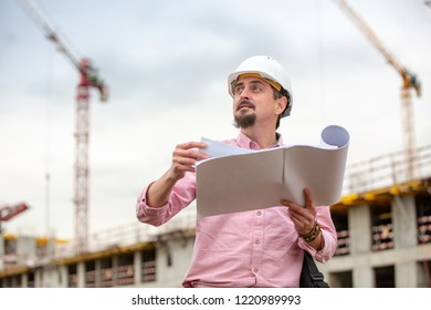 Portrait of architect at work with helmet in a construction site, reads the plan, paper projects