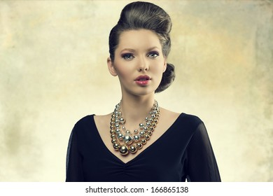 portrait of aristocratic fashion female posing with elegant hair-style, black dress and big necklace. Looking in camera with sensual eyes