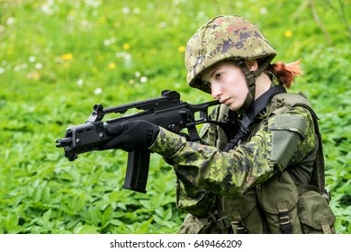 Portrait of armed woman with camouflage. Young female soldier observe with firearm. Child soldier with gun in war, green goutweed background.  Military, army people concept