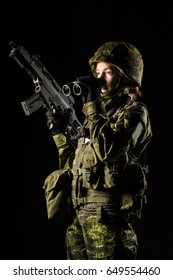 Portrait of armed woman with camouflage. Young female soldier observe with binoculars. Child soldier with gun in war, black background.  Military, army people concept