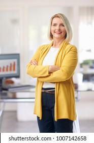 Portrait of an arms crossed smiling financial businesswoman standing at the office.