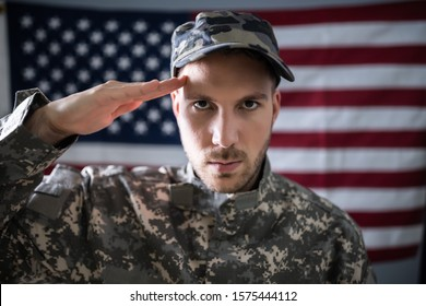 Portrait Of Army Soldier Saluting In Front Of American Flag