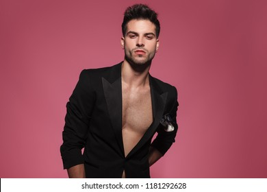 portrait of arrogant sexy man wearing only a black tuxedo and standing on red background