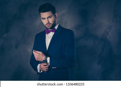 Portrait of arrogant sharp-dressed  rich man in blue suit correcting button on cufflink of shirt preparing for date meeting looking to the side isolated on grey background with copy space empty place