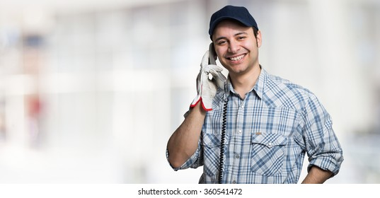 Portrait of an artisan talking on the phone. Large copy-space