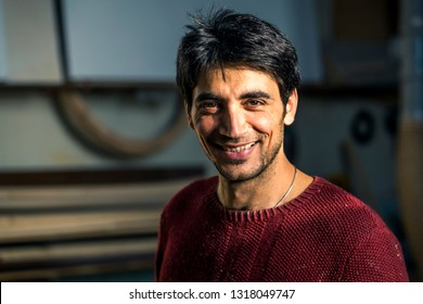 Portrait of an artist who is making this easels in his studio in Moscow, Russia. Talented armenian man in bordo swetshirt.