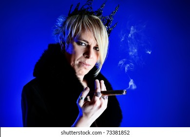 Portrait of an artistic young man in a king costume smoking a cigar. Studio shot.