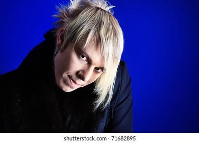 Portrait of an artistic young man. Studio shot over dark background.