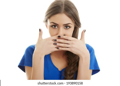 Portrait of ashamed young beautiful woman covering her mouth with both hands. Isolated on white background