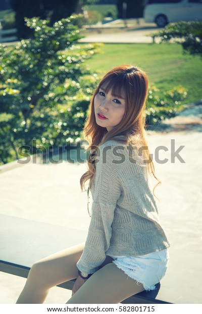 portrait of asia beautiful woman sitting on bench on sun