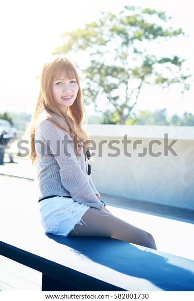 portrait of asia beautiful woman sitting on bench on sun