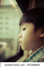 Portrait of asia boy looking out the window / Looking to the future