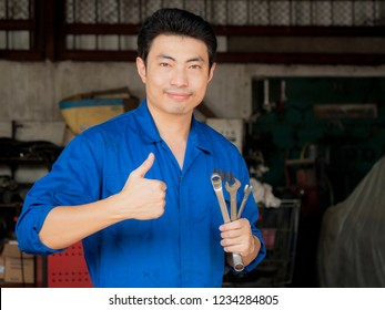 Portrait of asia young mechanic engineer holding wrench and standing in the garage with sweat from hot weather