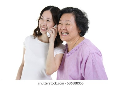 Portrait of Asian adult daughter calling on phone, sharing with senior mother and smiling, isolated on white background.